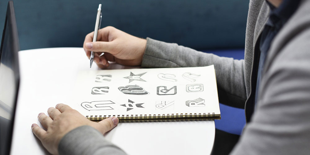 Logo designs drawn in sketchbook