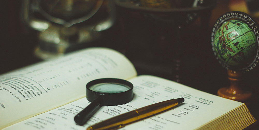 magnifying glass on top of notebook