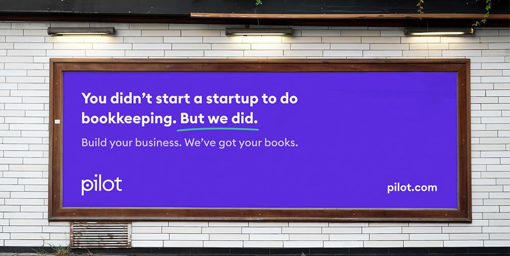 Purple billboard for Pilot on subway wall